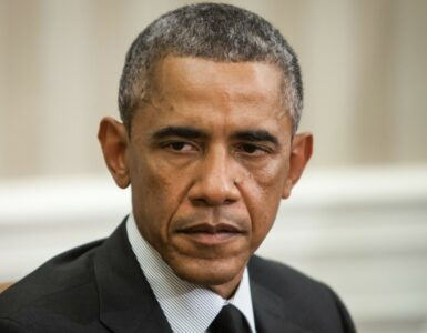 Barack obama wearing a dark suit and looking very tired