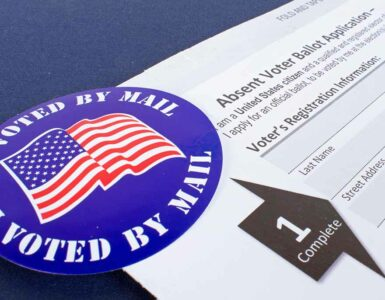 a mail in voting ballot and sticker